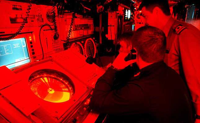 HMS TRIUMPH control room under red light.