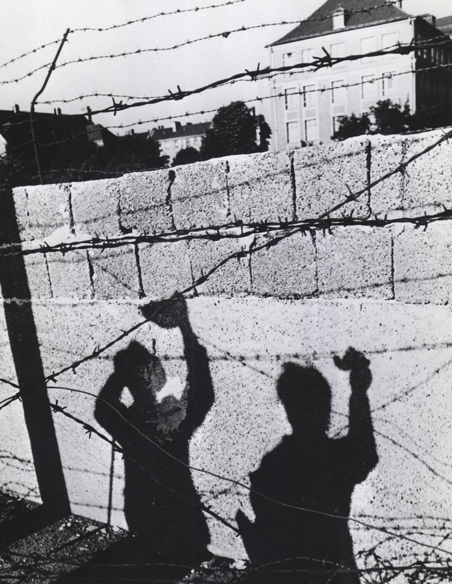 A picture is worth a thousand words: In October 1961, the shadows of two West Berliners waving to friends across the East-West border fall symbolically upon the concrete of the newly-built wall in a frame of barbed wire. Photo: U.S. Information Agency.